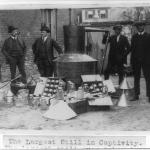 Lieutenant O.T. Davis, Sergeant J.D. McQuade, George Fowler of the IRS and H.G. Bauer posed with the largest bootlegging still confiscated until that date in 1922