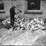 A man uses a firemen's axe to destroy alcohol confiscated during prohibitions raids throughout Detroit
