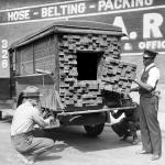 "Alerted by the smell of a broken bottle of liquor, Federal Agents inspect a ""lumber truck"". Los Angeles, 1926"